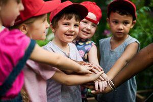 niños formando equipo chocando aire libre